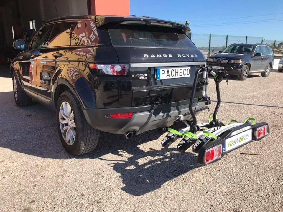 Portabicis con capacidad para tres bicicletas enganchado a la bola de remolque de un Range Rover Evoque.